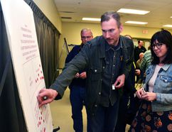 At the short term rental accommodation open house Monday night, residents were invited to vote on whether the city's draft zoning bylaw should allow for the rental of entire dwellings in which the owner does not live, and how those rentals should be regulated, if at all. Pictured, Jeremy Cox and Pamela Coneybeare use coloured stickers to vote.