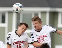 Cochrane High's Josiah Lipper (15) and Joe Bell climb over Bow Valley's Max Perron during their 2-2 draw.