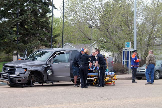 EMS attend to the driver of a Ford F150 following a collision in Millet last Friday.