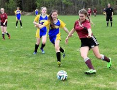 Sean Chase/Daily Observer Jaguar Brianna Mulvihill (right) fights Crusader Mackenzie Godin (centre) for possession of the ball during the junior girls soccer final. St. Joseph's scored a 1-0 win over Bishop Smith to take the county championship.