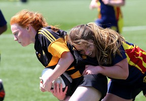 La Salle Black Knights' Dakota Sharpe tries to get out of the grasp of a Napanee Golden Hawks player during the Kingston Area Secondary Schools Athletic Association girls rugby championship at Nixon Field on Thursday. Napanee won the game, 18-15, in penalty kicks after the teams were tied through overtime.