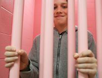 Morris Dubé of Mississauga poses behind cell bars in one of the pink-painted cells at the Stirling-Rawdon Police Service headquarters on Saturday May 20, 2017 in Stirling, Ont. Dubé was one of several taking a tour of the building as part of an SRPS open house. Tim Miller/Belleville Intelligencer/Postmedia Network