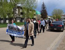 Rev. Donalee Williams (left) and Waj Arain (centre), co-founders of Collaboration for Religious Inclusion, hold up a banner for the Walk in Unity event as the group passes the Markaz ul Islam in Fort McMurray Alta. on Saturday May 20, 2017. Cullen Bird/Fort McMurray Today/Postmedia Network