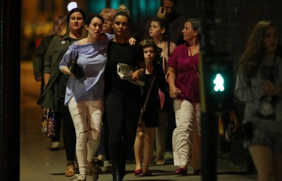 MANCHESTER, ENGLAND - MAY 23:  Police escort members of the public from the Manchester Arena on May 23, 2017 in Manchester, England.  There have been reports of explosions at Manchester Arena where Ariana Grande had performed this evening.  Greater Manchester Police have have confirmed there are fatalities and warned people to stay away from the area. (Photo by Christopher Furlong/Getty Images)
