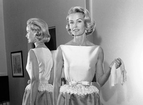 In this April 6, 1962 file photo, socialite-actress Dina Merrill models the gown she will wear at the Academy Awards presentation in Los Angeles. Merrill, the rebellious heiress who defied her super-rich parents to become an actress, died Monday, May 22, 2017, at age 93. (AP Photo/Harold P. Matosian, File)