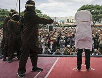 Shariah law official whips one of two men convicted of gay sex during a public caning outside a mosque in Banda Aceh, Aceh province, Indonesia, on Tuesday, May 23, 2017. (Heri Juanda/AP Photo)