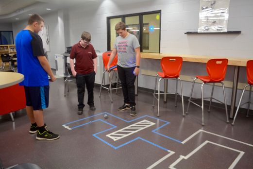 Tyson Rousseau, Bradlee Renton and Erich Zappel created a path which their Sphere-O bot follows based on the math and speed analysis the students have developed on their iPad, during the recent IGNITE Technology Fair that took place at St. Charles College last Thursday. Photo supplied