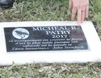 """Yves Poitras, principal of École secondaire catholique Thériault, kneels at the plaque that was unveiled in honour of teacher Michael Patry who died in February. The plaque was unveiled in the arboretum on the school grounds Wednesday night. The inscription on the plaque is the French translation of a quote by American author John Steinbeck who once said, """"Teaching might even be the greatest of the arts since the medium is the human mind and spirit."""""""