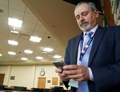 Luke Hendry/The Intelligencer Hastings County chief administrative officer Jim Pine holds his mobile phone after a council meeting Thursday in Belleville. He's also co-leader of the Eastern Ontario Regional Network, which aims to prepare the region for the arrival of ultra-fast 5G telecommunications networks.