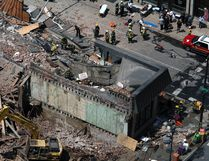 In this June 5, 2013 file photo rescue personnel search the scene of a building collapse in downtown Philadelphia. An arbitrator has awarded $95.6 million to a Ukrainian immigrant who was seriously injured in a 2013 Philadelphia building collapse. Mariya Plekan's attorney, Andrew Stern, announced the division of the $227 million settlement on Thursday, May 25, 2017. (AP Photo/Jacqueline Larma, File)
