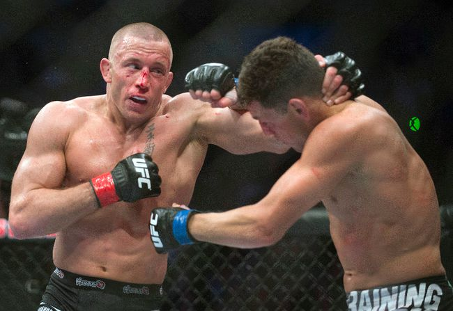 In this March 16, 2013, file photo, Georges St. Pierre, left, lands a blow to Nick Diaz during their UFC 158 welterweight title fight in Montreal. (Graham Hughes/The Canadian Press via AP, File)