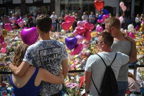 Couples comfort one another as flowers and balloons are left in Saint Ann's Square in tribute to those killed in an explosion at the Manchester Arena earlier this week on May 26, 2017 in Manchester, England. (Anthony Devlin/Getty Images)