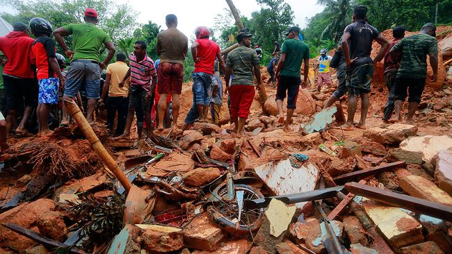 Sri Lankan military rescuers and villagers stand on the debris of a house that was destroyed in a landslide in Bellana village in Kalutara district, Sri Lanka, Friday, May 26, 2017.  (AP Photo/Eranga Jayawardena)