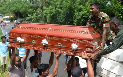 Villagers load a coffin containing a landslide victim onto an army armoured personnel carrier being used in rescue operations at Bulathsinhala in Kalutara district on May 27, 2017. (LAKRUWAN WANNIARACHCHI/AFP/Getty Images)
