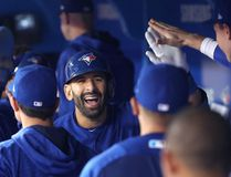 Jose Bautista of the Blue Jays is congratulated by teammates in the dugout after hitting a three-run home run against the Texas Rangers at Rogers Centre on May 27, 2017 in Toronto. (Tom Szczerbowski/Getty Images)