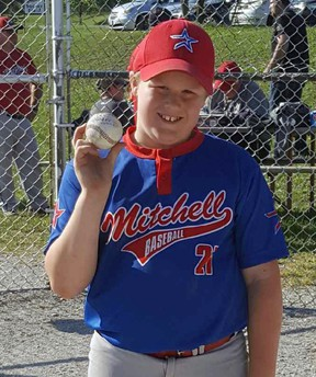 Lucas Roobroeck holds the ball he hit out of the park in Holmesville, highlighting the Mitchell Mosquito's OBA team's tournament championship in Clinton this past weekend. SUBMITTED