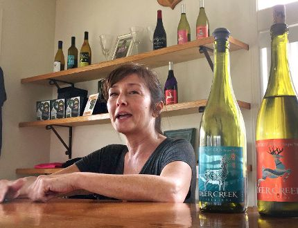 In this April 5, 2017 photo, vineyard owner Katherine Bryan laughs as she discusses the wines available for tasting at Deer Creek Vineyards in Selma, Ore. Bryan is one of a handful of vineyard owners and winemakers in this fertile corner of southwestern Oregon who are branching out into marijuana farming after the legalization of recreational weed in Oregon two years ago. (AP Photo/Gillian Flaccus)