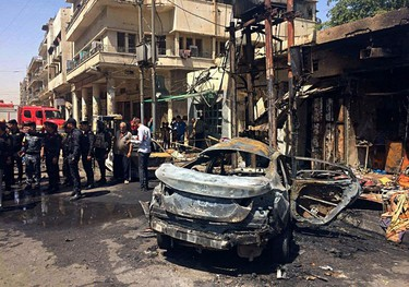 Iraqi security forces and civilians inspect the site of a deadly bomb attack, in Baghdad, Iraq, Monday, May 30, 2017. Another bomb exploded outside a popular ice cream shop in the Karrada neighborhood of Baghdad just after midnight on Monday, killing and wounding dozens of civilians, hospital and police officials said. (AP Photo/Karim Kadim)