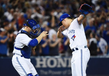 Toronto Blue Jays catcher Russell Martin (55) and Blue Jays relief pitcher Roberto Osuna (54) celebrate their victory over the Cincinnati Reds in MLB interleague baseball action in Toronto on Tuesday, May 30, 2017. THE CANADIAN PRESS/Nathan Denette ORG XMIT: NSD525