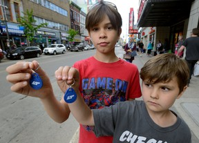 Xander Logan, 9, and his brother Micah, 5, of London show the key fobs they use to ride free on LTC buses Wednesday. (MORRIS LAMONT, The London Free Press)