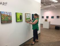 Centre for Creative Arts executive director Candace Hook hangs some of the works in the Art Squared exhibit, which opens Friday.Supplied