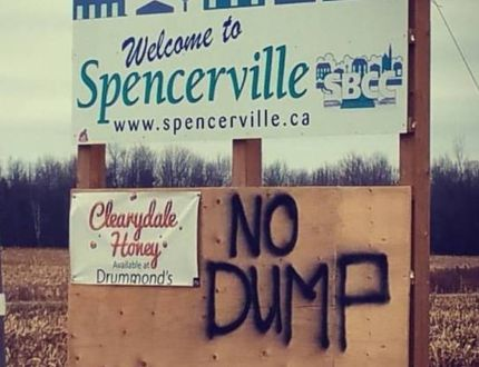 A 'No Dump' protest is painted on a sign outside the village of Spencerville.