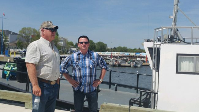 RM of Gimli mayor Randy Woroniuk with Gimli MLA Jeff Wharton stand next to a boat in the Gimi Harbour in Gimli, Man., on Friday, June 2, 2017. (Juliet Kadzviti/Interlake Spectator/Postmedia Network)