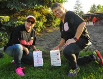 """Mother-daughter duo Stacy and Sheila Botting of Simcoe place luminary bags in Wellington Park as part of the Canadian Cancer Society's Luminaries for Life event Friday night. A host of bags containing plastic candles were arranged to spell """"hope"""" and """"cure"""" before being lit at nightfall. JACOB ROBINSON/Simcoe Reformer"""
