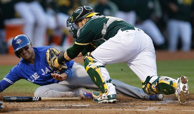 Oakland Athletics catcher Stephen Vogt, right, tags out Toronto Blue Jays' Ryan Goins at home plate in the third inning of a baseball game Tuesday, June 6, 2017, in Oakland, Calif. (AP Photo/Ben Margot) ORG XMIT: OAS106