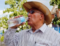 <p>Bartolome Matamoros of Belleville, Ont. takes multiple precautions against the heat in this 2016 file photo: drinking water; wearing a hat, long sleeves and sunglasses; and finding shade during a break from his walk.</p><p> Luke Hendry/Belleville Intelligencer/Postmedia Network