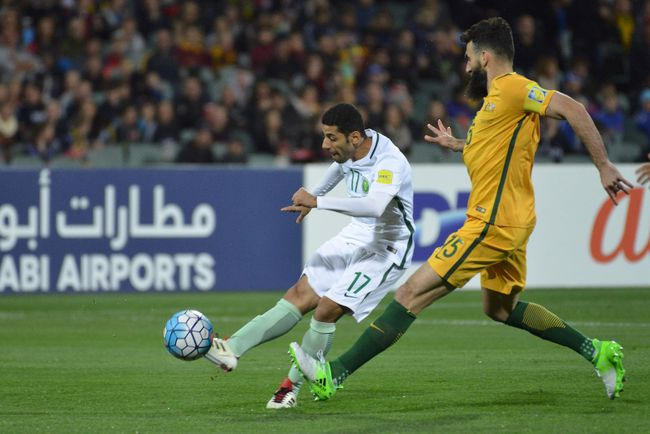 Taiseer al Jassam of Saudi Arabia fights for the ball with Mile Jedinak of Australia during the World Cup football Asian qualifying match between Australia and Saudi Arabia at the Adelaide Oval in Adelaide on June 8, 2017. / AFP PHOTO / Brenton Edwards