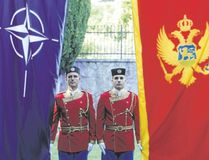Montenegrin honour guards stand next to NATO and Montenegrin flags during a ceremony in the capital Podgorica Wednesday. Montenegro became NATO's 29th member on Monday just as the crucial Atlantic alliance appeared imperilled by the U.S. president's ambiguous commitment to its mutual defence. (SAVO PRELEVIC/Agence France Presse)