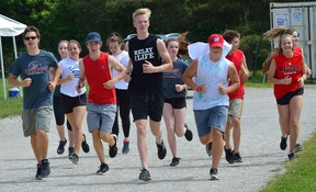 Students from Medway secondary school jog around their cinder track Friday during a fundraiser to help raise money for a new track-and-field facility at the school. The facility will be built in memory of late student athlete Roy Davis. (MORRIS LAMONT, The London Free Press)