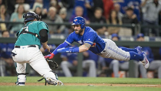 Toronto Blue Jays' Kevin Pillar dives for home plate as Seattle Mariners catcher Mike Zunino makes a tag during the seventh inning of a out game at Safeco Field on June 9, 2017 in Seattle, Wash. (Stephen Brashear/Getty Images)