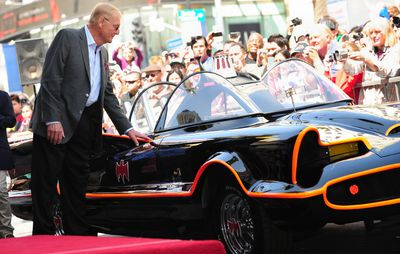 Adam West, who played Batman in the original TV series, touches the Batmobile as a crowd gathers to watch as West receives his star on Hollywood's Walk of Fame on April 5, 2012 in Hollywood, Calif. (FREDERIC J. BROWN/AFP/Getty Images)