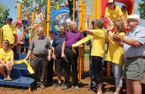 Shawn Pearce (blue shirt), president of Inverary Youth Activities Inc., South Frontenac Mayor Ron Vandewal (purple shirt), Judy Borovski, chairperson of the Playground Committee and many volunteers celebrate the opening of a brand-new play structure at Ken Garrett Park in Inverary on Saturday. (Steph Crosier/The Whig-Standard)