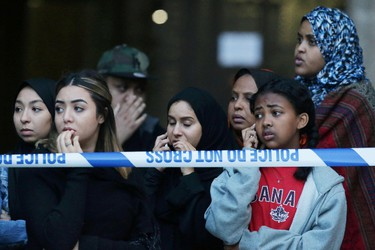 """TOPSHOT - Local residents watch as Grenfell Tower is engulfed by fire on June 14, 2017 in west London.  The massive fire ripped through the 27-storey apartment block in west London in the early hours of Wednesday, trapping residents inside as 200 firefighters battled the blaze. Police and fire services attempted to evacuate the concrete block and said """"a number of people are being treated for a range of injuries"""", including at least two for smoke inhalation.   / AFP PHOTO / Daniel LEAL-OLIVASDANIEL LEAL-OLIVAS/AFP/Getty Images"""