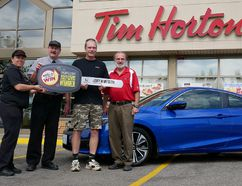 Simcoe's Jerry Antoszek won a Honda Civic during this year's Tim Hortons Roll Up the Rim to Win promotion. The official presentation was made Wednesday morning in Tillsonburg where Antoszek bought the winning large regular double-double. From left are Sheila Klassen, manager of the Simcoe Street Tim Hortons; Randy Salverda, owner of the Tillsonburg Tim Hortons franchises; Antoszek; and Darryl Lazowski, owner of Simcoe Honda.Chris Abbott/Tillsonburg News