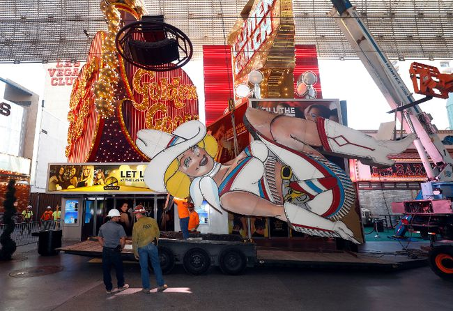 "Workers remove the neon sign dubbed ""Vegas Vickie"" in downtown Las Vegas, Tuesday, June 13, 2017. The sign was taken down as part of the construction for a new resort-casino. (Steve Marcus /Las Vegas Sun via AP)"