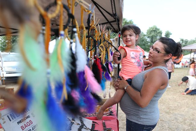 Mya Manicowabi-Hicks and her mother Tanya Manicowbi look at dream catchers from sale from Twila Authentic Crafts during the Caldwell First Nations Pow Wow in Leamington, Ontario on August 12, 2016. (JASON KRYK/Windsor Star)