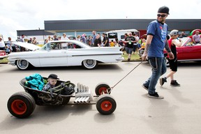 Joseph Baillargeon and his sons Baker Baillargeon, 1, and Caden Evans, 9, take in the 16th Annual Father's Day Show and Shine Car Show at Celebration Church, 7215 Argyll Road, Sunday June 18, 2017. Photo by David Bloom