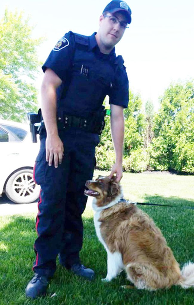 Const. Weber of the Greater Sudbury Police poses with a dog he rescued from a hot vehicle on Friday. (Photo supplied)