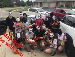 """This group of students caused a stir at Holy Trinity Catholic High School in Simcoe last week when – as a prank – they stormed the cafeteria wearing """"Purge"""" masks and brandishing water pistols. Administrators at the high school and the Brant Haldimand Norfolk Catholic District School Board continue to review the incident. (Facebook photo)"""