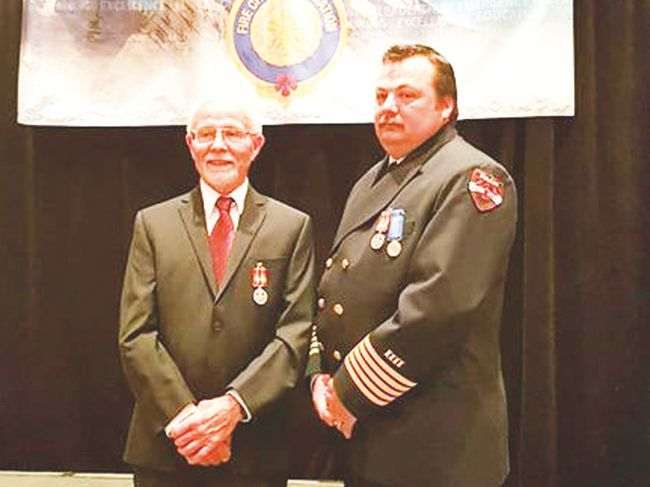 Retired Champion Fire Chief Doug Grant, left, stands with son Aaron. Both received the Exemplary Service medals for 20 years of fire service.
