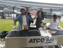 Tarun Malik (left), a community disability services practitioner, helps work the barbecue at the ECHO Society fundraiser (Jeremy Appel | Whitecourt Star).