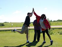 Golfer Dean Chapman from FrontLine Financial and Benefit Service high-fives fellow teammate Geraldine Chitate from ChiM Cement and Concrete at the Montgomery Glen Golf Course and Country Club June 15.