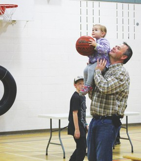 Dad Daniel Hartley helps his youngest daughter, Helen, shoot a basket at St. Anthony School's annual Doughnuts for Dads event held in the school gymnasium.