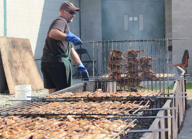 Pine River Chicken BBQ brings hundreds together at the Ripley arena to raise money for the Pine River United Church. The event brings up to six hundred people for homemade food and celebrates it's sixth year of success. Rows of chicken could be found on the BBQ behind the Ripley arena with stacks of volunteers helping to run the show. Pictured: A BBQ operation more the 30ft long keeps volunteers turning fresh chicken.  (Ryan Berry/ Kincardine News and Lucknow Sentinel)
