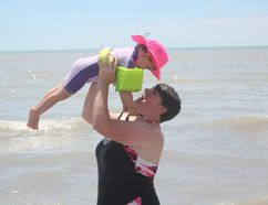 Jaci Oliver holds up Alexandra, 2, at the Port Stanley main beach on Wednesday afternoon. Lake Erie's average water level for May was at an all time high. (Laura Broadley/Times-Journal)