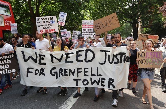 "Demonstrators hold a banner demanding justice for the victims of the recent deadly apartment block fire at Grenfell Tower, as they march towards parliament in central London Wednesday June 21, 2017. The mass ""Day of Rage"" demonstration is timed to coincide with the state opening of parliament Wednesday. (AP Photo / Matt Dunham)"